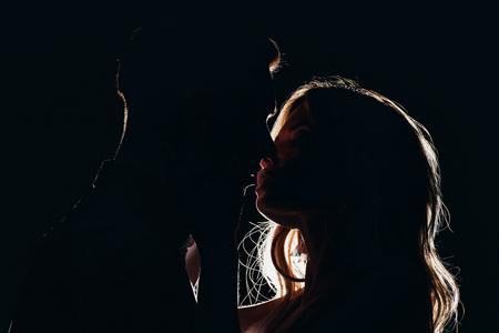 Photo pour silhouettes of sensual heterosexual couple kissing in dark - image libre de droit