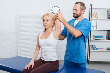 Smiling chiropractor stretching woman arm on massage table in clinic