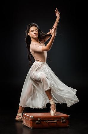 Foto de Elegant female ballet dancer in white skirt dancing on dark background - Imagen libre de derechos