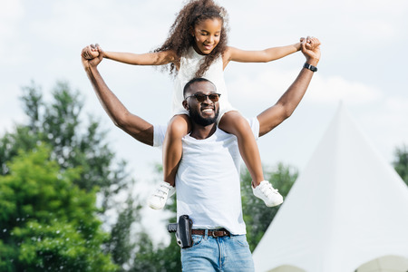 Photo pour Happy african american police officer with gun holding daughter on shoulders in amusement park - image libre de droit