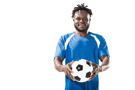 Foto de African american soccer player holding ball and smiling at camera isolated on white - Imagen libre de derechos