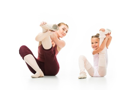 Photo pour Happy little ballerina and her female trainer stretching legs isolated on white background - image libre de droit