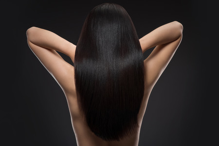 Photo pour Back view of woman with beautiful shiny hair isolated on black - image libre de droit