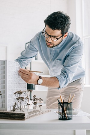 Photo pour handsome architect working with architecture model on table in office - image libre de droit