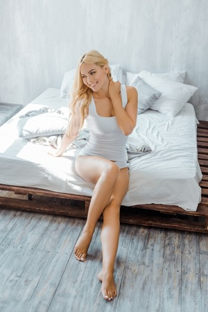 Photo pour high angle view of beautiful smiling girl in underwear sitting on bed and looking away - image libre de droit