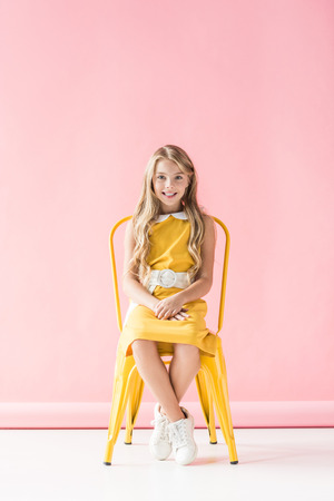 Foto per happy fashionable adorable youngster sitting on yellow chair on pink - Immagine Royalty Free
