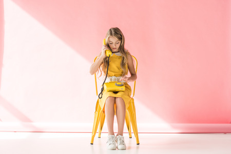 Foto de fashionable kid making call on retro phone while sitting on yellow chair on pink - Imagen libre de derechos