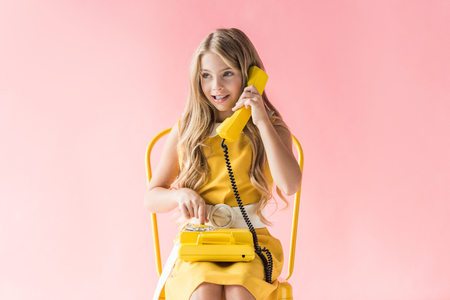 Foto de adorable smiling child making call on yellow rotary phone while sitting on chair on pink - Imagen libre de derechos