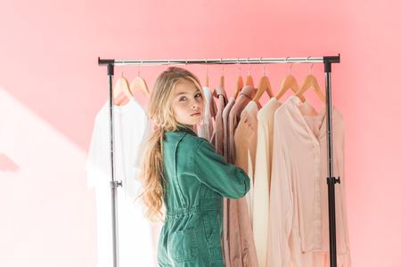 Foto de attractive female child in trendy overalls choosing clothes on hangers - Imagen libre de derechos
