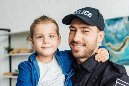 Foto de happy young father in police uniform carrying his little son and looking at camera - Imagen libre de derechos