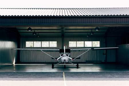 Photo pour small modern white airplane standing in hangar - image libre de droit