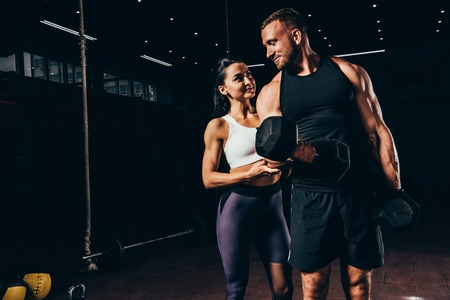 athletic sportsman exercising with barbell and flirting with sportswoman in dark gym