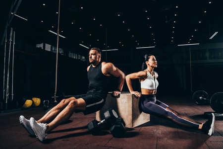 Foto de athletic sportsman and sportswoman exercising on cube together in dark gym - Imagen libre de derechos