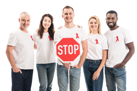 Photo for group of people in blank white t-shirts with aids awareness red ribbons and stop road sign looking at camera isolated on white - Royalty Free Image