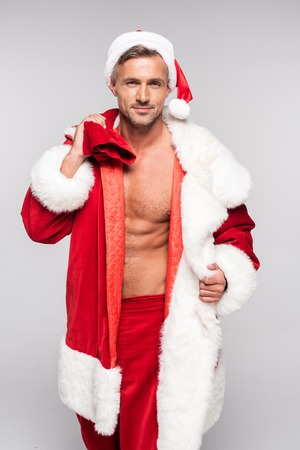 Foto de Handsome man in Santa costume holding bag with presents and looking at camera isolated on grey background - Imagen libre de derechos