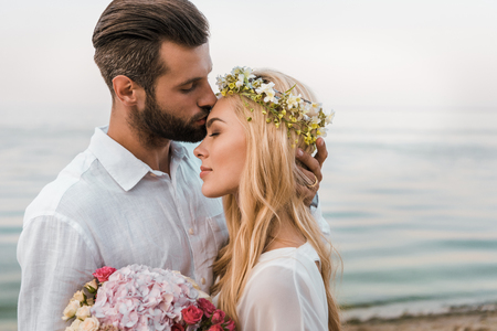Photo pour Side view of handsome groom kissing attractive bride forehead on beach - image libre de droit