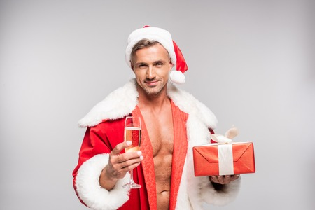 Photo pour Smiling sexy Santa holding glass of champagne and gift box isolated on grey background - image libre de droit