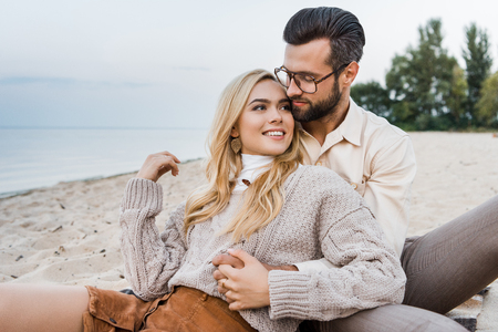 Foto de Smiling girlfriend and boyfriend in autumn outfit sitting and hugging on beach - Imagen libre de derechos