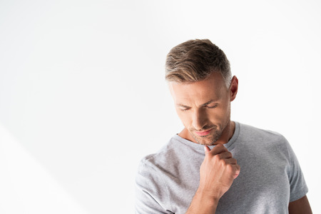 Foto de Thoughtful adult man in blank grey t-shirt touching his chin and looking down isolated on white background - Imagen libre de derechos
