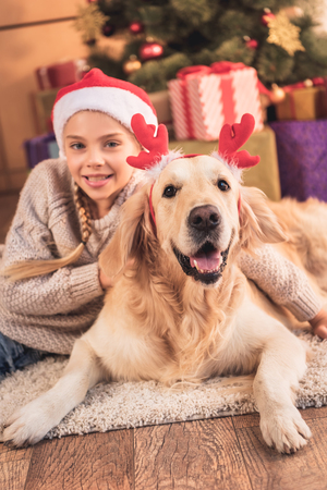 Foto de Smiling child in Santa hat and golden retriever dog with deer horns lying near Christmas presents - Imagen libre de derechos