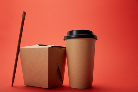 Photo pour close up view of noodle box, paper cup of coffee with chopsticks on red, minimalistic concept - image libre de droit