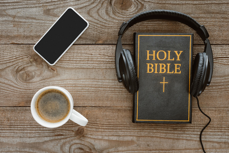Photo for top view of holy bible with headphones, smartphone and coffee on wooden tabletop - Royalty Free Image