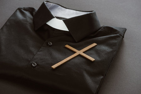 Photo pour close-up shot of clerical shirt with cross on grey surface - image libre de droit