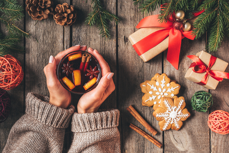 Photo for cropped view of woman holding glass with hot mulled wine on wooden background with christmas gifts - Royalty Free Image
