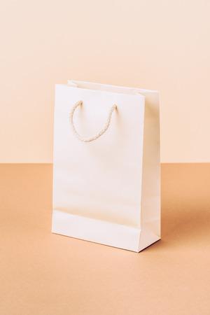 Foto de white paper shopping bag on beige - Imagen libre de derechos