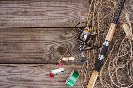 Foto de top view of reel, fishing rod, bait and fishing net on wooden background - Imagen libre de derechos