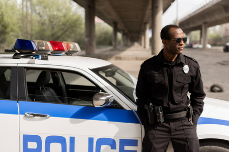Photo for african american police officer leaning back on car and looking away - Royalty Free Image