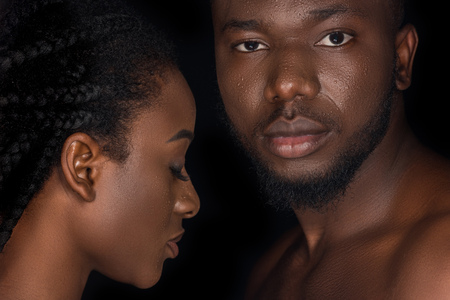 Foto de beautiful young african american couple with water drops on faces posing isolated on black - Imagen libre de derechos
