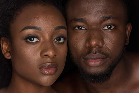Foto de young african american couple with water drops on faces looking at camera on black - Imagen libre de derechos