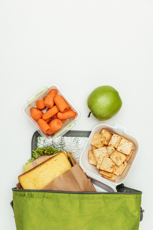 Foto de top view of sandwich and carrots with apple in lunch bag isolated on white - Imagen libre de derechos