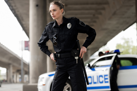 Photo for confident female police officer looking away and taking out gun and bat - Royalty Free Image