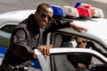 Photo for happy young police officers with car looking at camera - Royalty Free Image