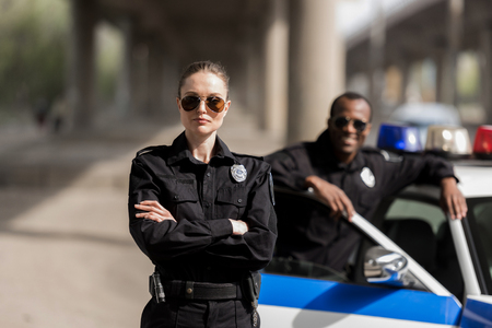 Foto de young serious policewoman standing with crossed arms while her partner standing near car and smiling blurred on background - Imagen libre de derechos
