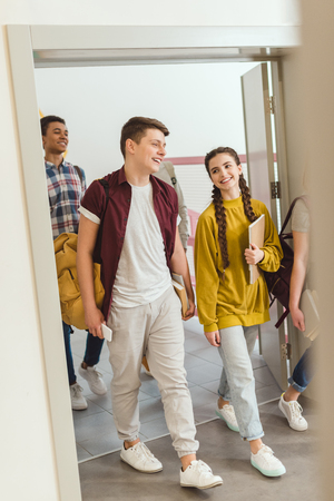 Foto de Multiethnic group of high school students walking by school corridor on break - Imagen libre de derechos