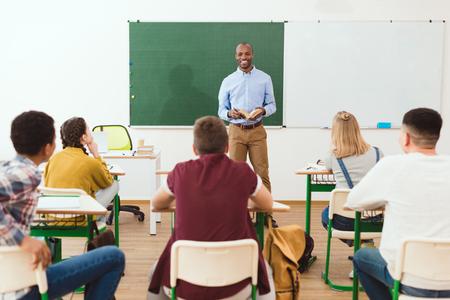Foto de Rear view of high school teenage students listening African American teacher with book in classroom - Imagen libre de derechos