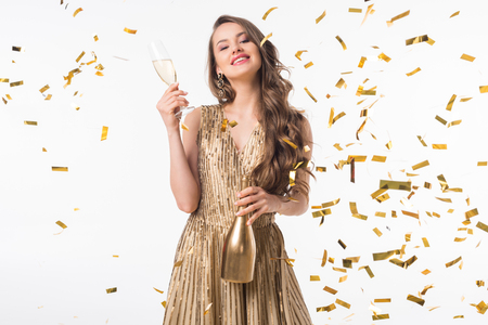 Photo for Smiling attractive woman standing with champagne under falling confetti isolated on white background - Royalty Free Image