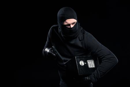 Photo pour Burglar in balaclava holding gun and locked safe box - image libre de droit
