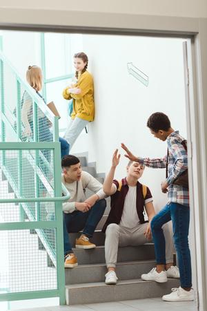 Foto de Group of high school students spending time on stairs at school together on break - Imagen libre de derechos