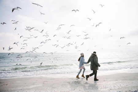 Foto de Young couple holding hands and walking on winter sea shore and looking at seagulls - Imagen libre de derechos