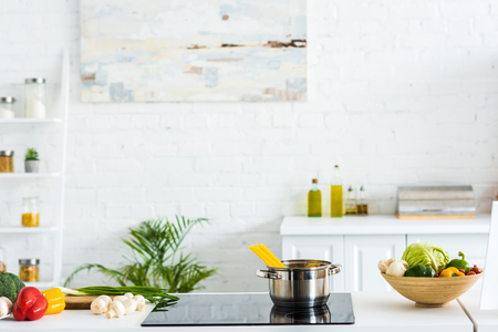Photo pour Interior of modern light kitchen with paint on wall and electric stove - image libre de droit