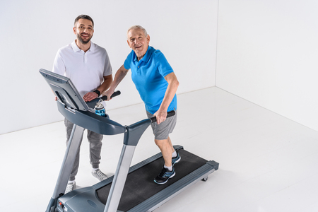 high angle view of rehabilitation therapist assisting senior man exercising on treadmill