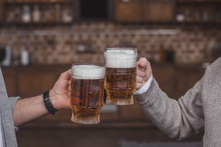 Photo for cropped image of adult son and senior father clinking with beer glasses at home - Royalty Free Image