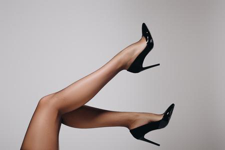 Foto de Female legs in black stockings and heel shoes isolated on grey background - Imagen libre de derechos
