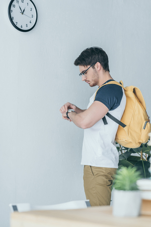 Photo pour handsome male student with backpack looking at wristwatch - image libre de droit