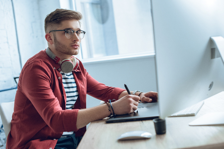 Photo pour Thoughtful freelancer working by table with graphic tablet - image libre de droit