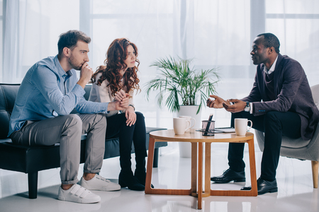 Photo pour Smiling african american psychiatrist talking to young couple in office - image libre de droit